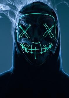 Homem anônimo, escondendo o rosto atrás da máscara de néon em uma fumaça colorida