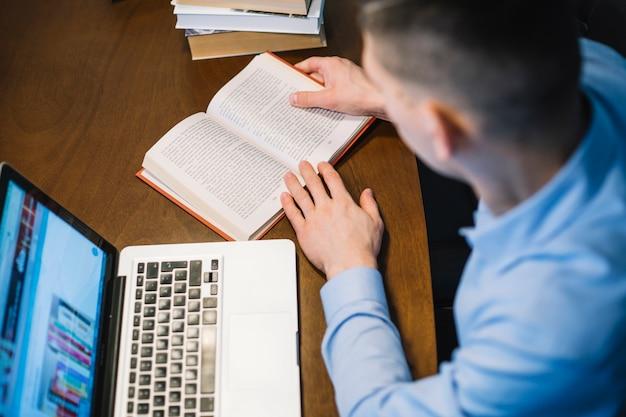 Homem anônimo lendo livro perto de laptop