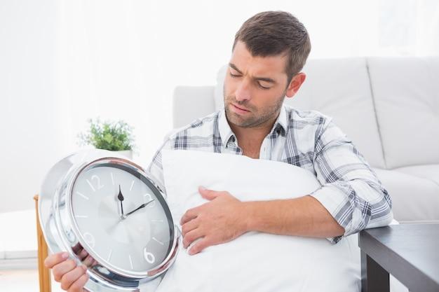 Homem ansioso ao lado de um relógio