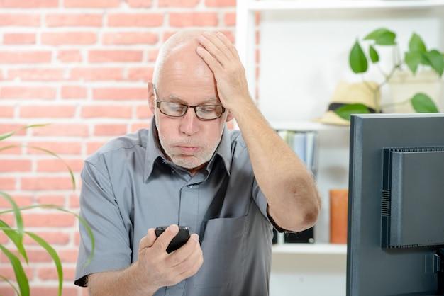 Homem ansioso olha para o seu smartphone