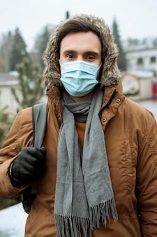 Homem ao ar livre no inverno usando máscara médica