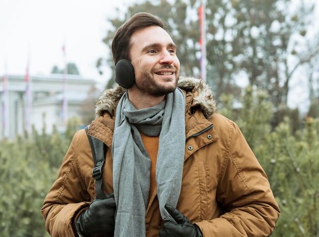 Homem ao ar livre no inverno usando protetores auriculares
