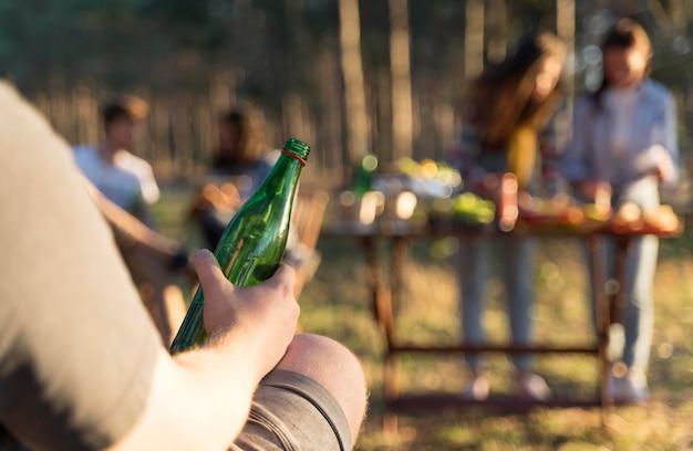 Homem ao ar livre segurando uma garrafa de cerveja com os amigos à mesa