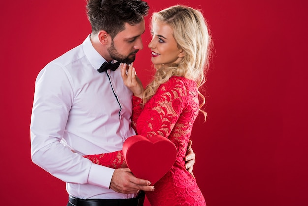 Homem ao lado da mulher em fundo vermelho