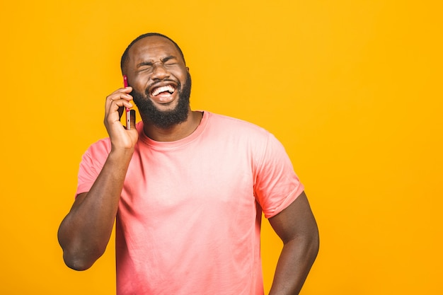 Homem ao telefone. homem negro alegre falando no telefone celular e sorrindo em pé isolado em fundo amarelo.
