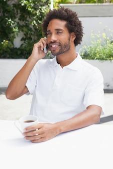 Homem ao telefone tomando café