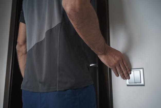 Homem apaga a luz ao sair da sala