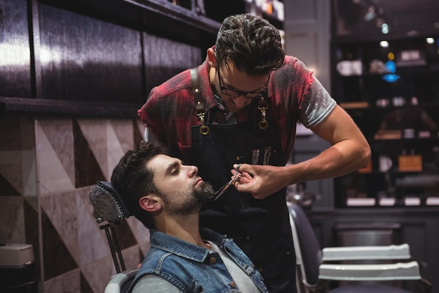 Homem aparando a barba com tesoura