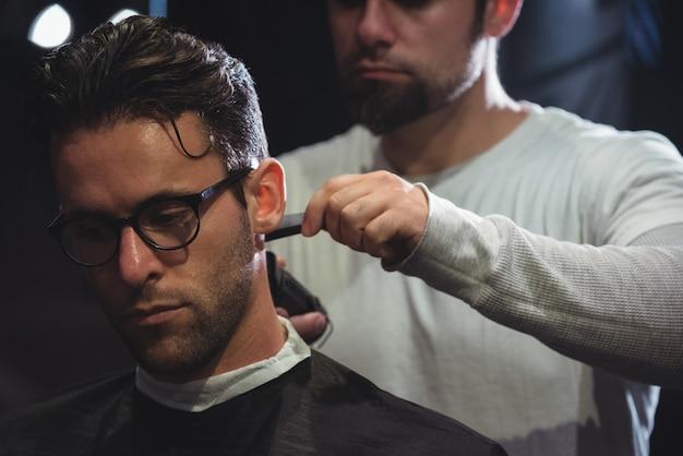 Homem aparando o cabelo com aparador