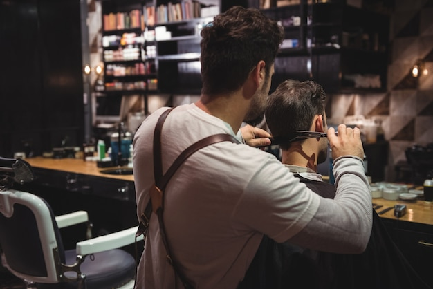 Homem aparando o cabelo com tesoura