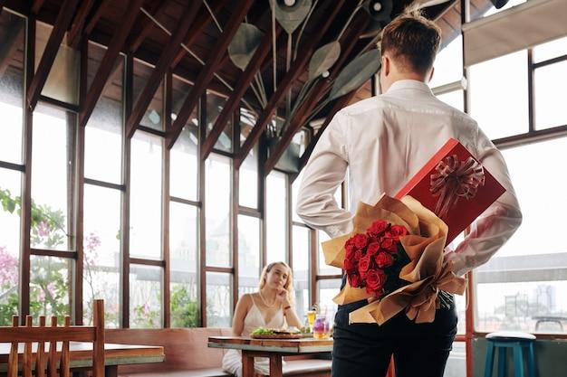 Homem aparecendo para um encontro com presentes