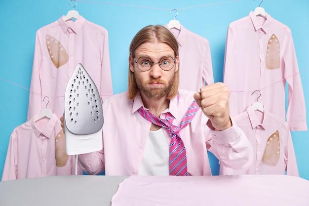 Homem aperta o punho olha furiosamente segura vestidos de ferro elétrico a vapor para o trabalho sente poses irritadas perto da tábua de passar roupas queimadas em cabides atrás