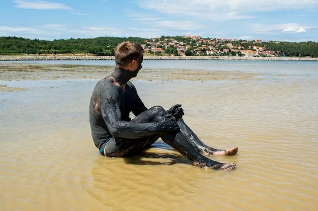 Homem aplicando argila cicatrizante preta