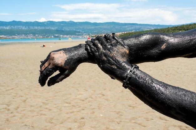 Homem aplicando argila preta de cura. relaxando no spa resort