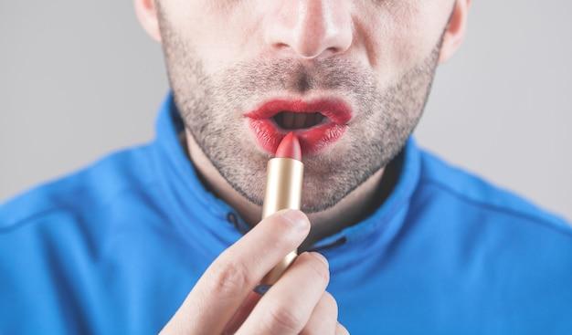 Homem aplicando batom vermelho nos lábios.