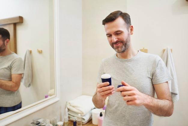 Homem aplicando desodorante nas axilas