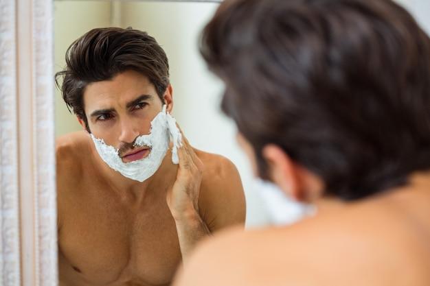 Homem aplicando espuma de barbear