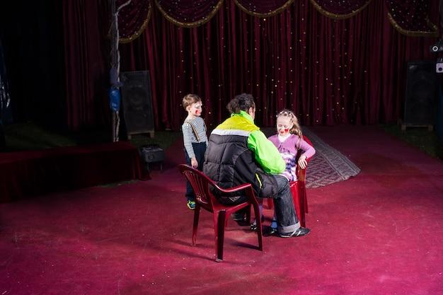 Homem aplicando maquiagem no rosto de um menino e uma menina no palco vazio