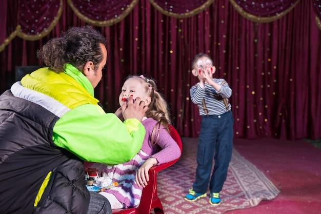 Homem aplicando maquiagem no rosto de uma loira sentada na cadeira enquanto o jovem garoto palhaço assiste do palco no fundo