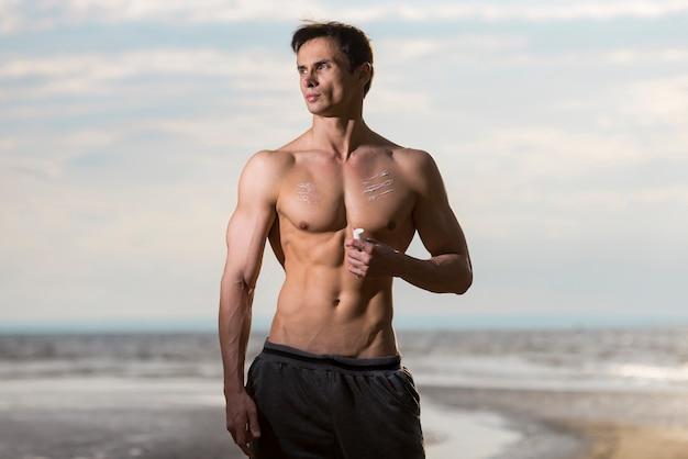 Homem, aplicando, protetor solar, loção, em, praia