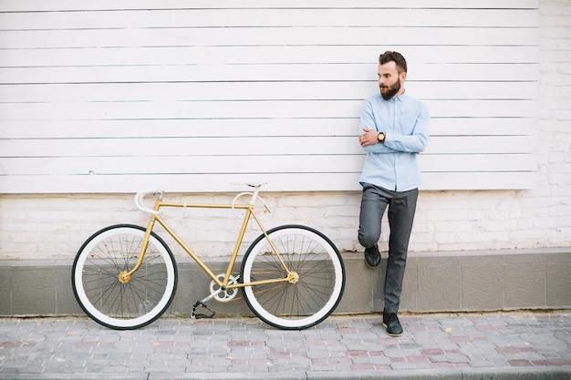 Homem apoiado na parede branca perto da bicicleta