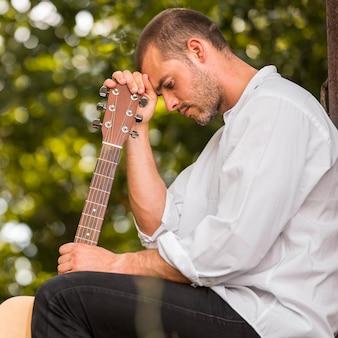 Homem apoiando a cabeça no cabeçote da guitarra