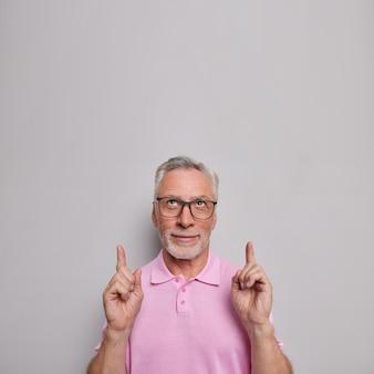 Homem aponta o dedo indicador para cima e dá conselhos sobre o que escolher demonstra entusiasmo promoção usa óculos transparentes camiseta casual apresenta promoção de loja online