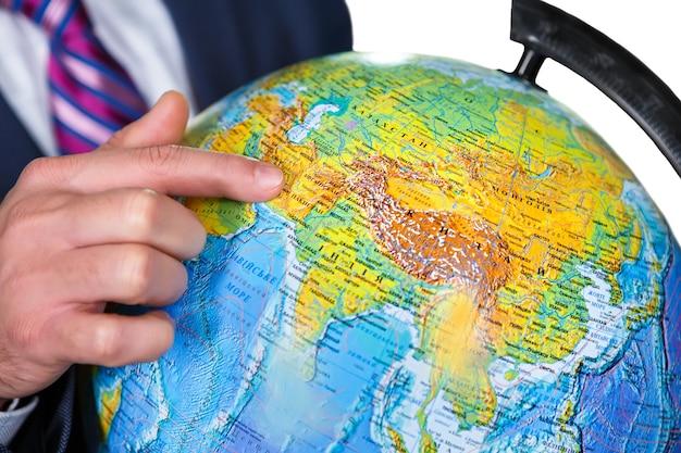 Homem aponta para o globo. este é o lugar onde vivemos. observe o globo. nosso lar.