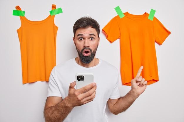 Homem aponta para roupas laranjas coladas na parede usa telefone celular para vender roupas desnecessárias online usa camisetas brancas casuais poses dentro de casa