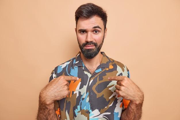 Homem aponta para si mesmo pergunta quem me tem atenção olha a câmera veste camisa coloful surpresa sendo escolhida isolada em bege.