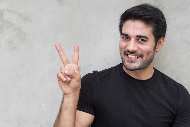 Homem apontando dois dedos, sinal de vitória v
