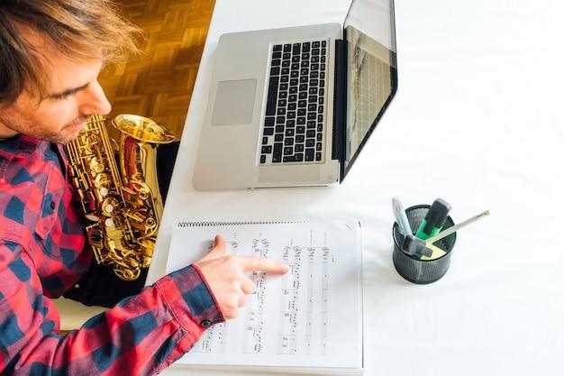 Homem apontando notas em partituras durante seu curso online de saxofone