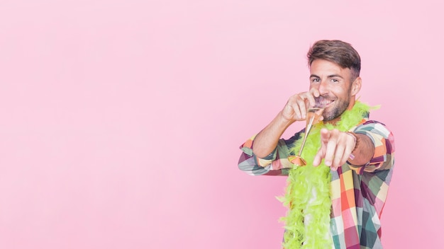 Homem apontando o dedo enquanto bebe vinho no fundo rosa