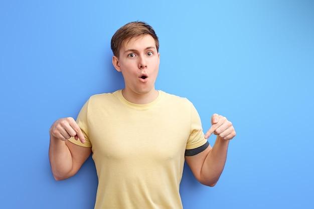 Homem apontando o dedo indicador para baixo, retrato de estúdio isolado, homem bonito em uma camiseta casual olhando para a câmera em estado de choque, surpreso