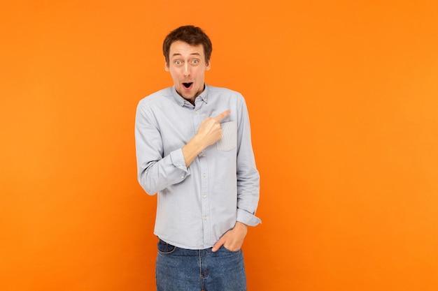 Homem apontando o dedo para a boca aberta do espaço da cópia e olhando para a câmera tem um olhar surpreso