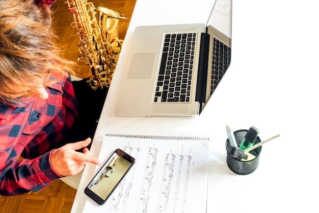 Homem apontando o telefone enquanto faz o curso de saxofone online