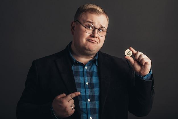 Homem apontando para bitcoin dourado na mão, símbolo digital da nova moeda virtual