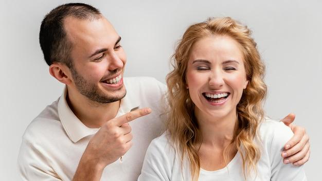 Homem apontando para mulher rindo