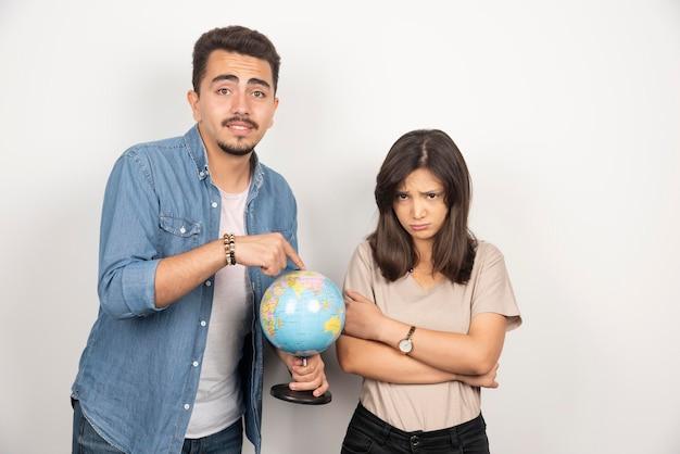Homem apontando para o globo terrestre ao lado de uma garota ressentida.