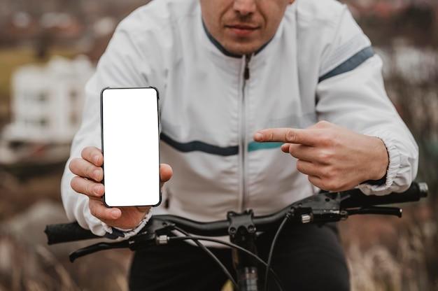 Homem apontando para seu telefone em branco