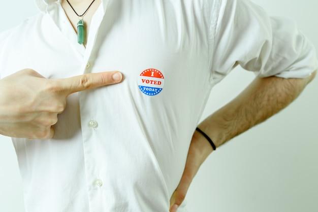 Homem apontando para um adesivo que eu votei hoje em seu peito.