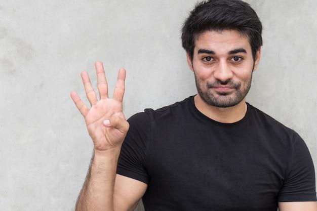 Homem apontando quatro dedos, contando, numerando, levantando o ponto