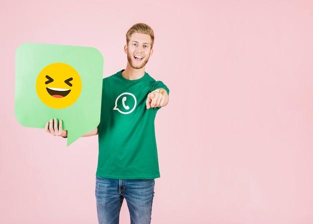 Homem, apontar, seu, dedo, enquanto, segurando, fala, bolha, com, sorrindo, emoji