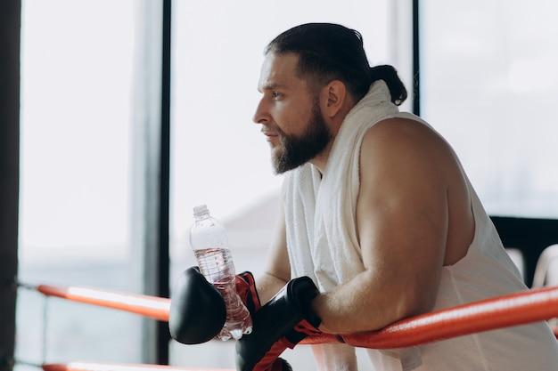 Homem após treinamento duro. boxer, dando um tempo bebendo da garrafa de água após o treino no ginásio