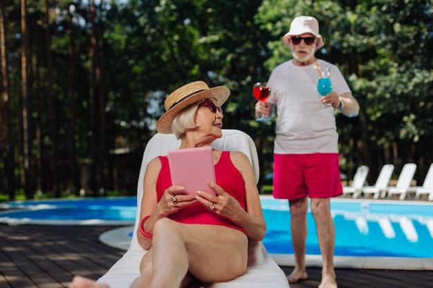 Homem aposentado atencioso trazendo alguns coquetéis de verão para a esposa tomando banho de sol perto da piscina