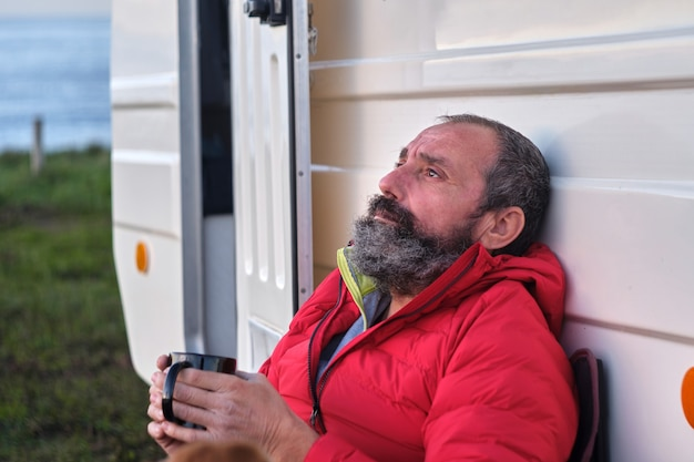 Homem aposentado com as mãos bebendo uma bebida quente na natureza