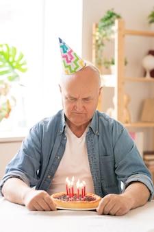 Homem aposentado com boné de aniversário fazendo um pedido na frente de um bolo com velas perto da mesa