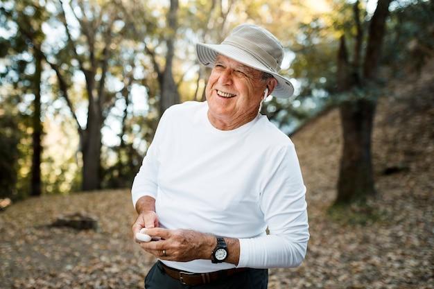 Homem aposentado curtindo música no meio da floresta