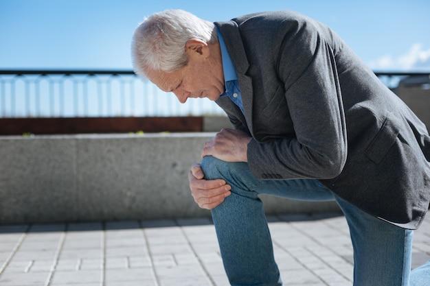 Homem aposentado elegante e doente tocando seu joelho e expressando descontentamento enquanto caminha ao ar livre