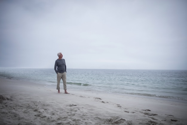 Homem aposentado pensativo em pé na praia